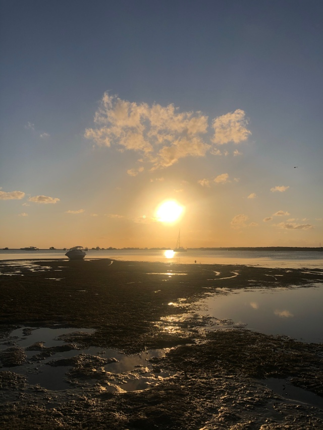 Sun setting over a beach at low tide